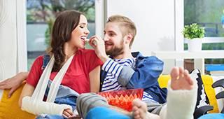 Man und Frau mit Gips sitzen auf einem Sofa