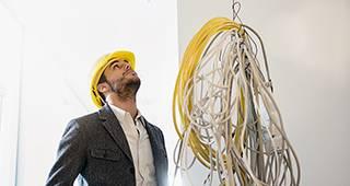 Ein Mann baut einen Turm aus Gegenständen im Büro