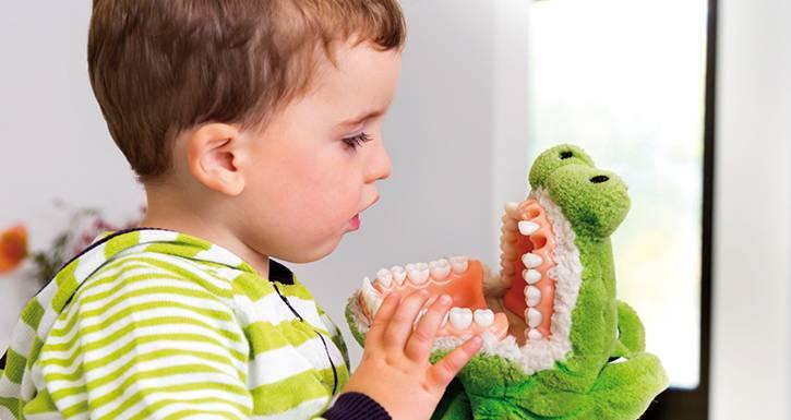 Baby schaut sich die Zähne seines Stofftiers genau an