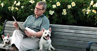 Kapitallebensversicherun: Mann sitzt mit Hunden auf Parkbank