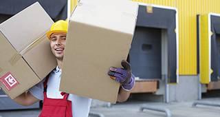 Transportversicherung: Ein Mann trägt zwei Pakete.