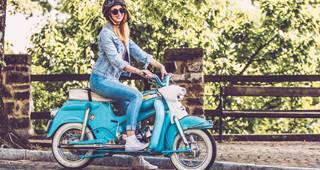 Junge Frau mit Moped