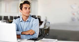 Anwartschaftsversicherung: Polizist sitzt am Schreibtisch