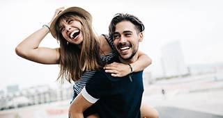 Ein Mann trägt eine Frau lachend Huckepack