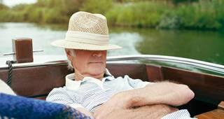 Unfallversicherung für Senioren: Mann mit Hut ein einem Boot