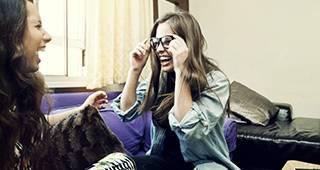 Zwei Frauen haben Spaß beim Anprobieren einer Brille