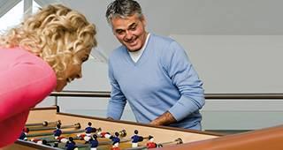 Beihilfeversicherung: Zwei Personen spielen Kicker