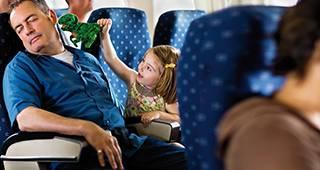 Mann mit privater Krankenversicherung schläft unbekümmert im Zug