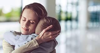 Mutter hält ihr Kind schützend im Arm