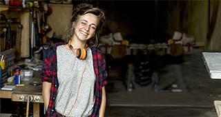 Versicherungspaket für Handwerker: Eine Frau steht mit Kopfhörern in einer Werkstatt.