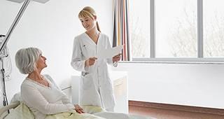 Krankenhaustagegeldversicherung: Ärztin untersucht Patientin