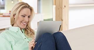 Bescheinigungen: Frau sitzt mit Tablet auf dem Sofa