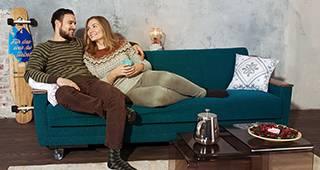 ISI-gesund: Junges Paar sitzt auf Sofa