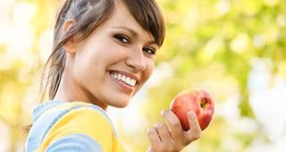 Frau mit Apfel lacht